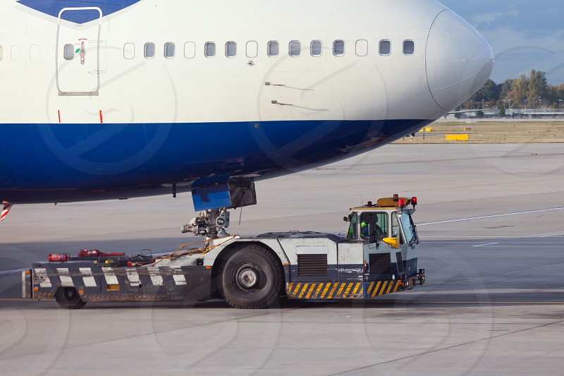 Large aircraft being pulled by airport tug tractor taxing on airfield into docking position for passenger boarding the airplane photo