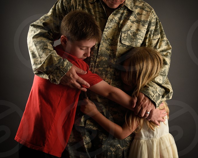 An army soldier man is home and hugging his children for a love family or reunited concept. photo