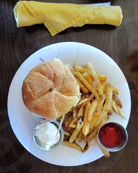Burger fries and condiments with napkins on wood tabletop photo