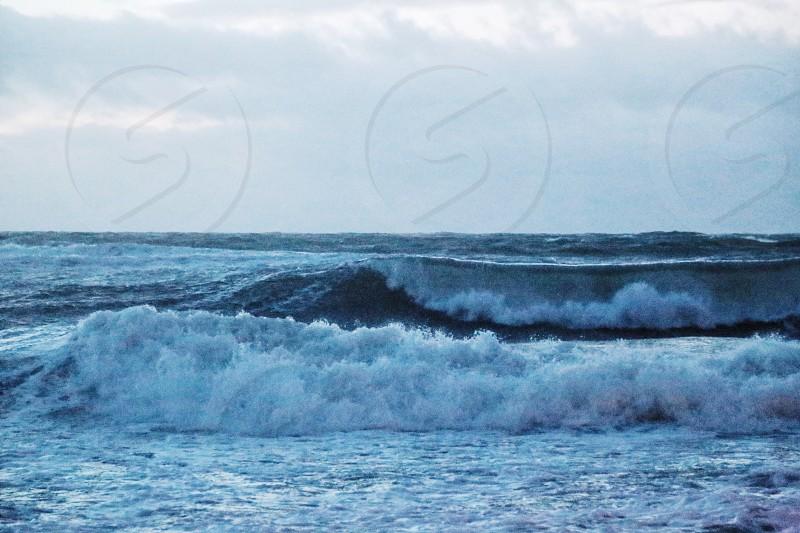 sea waves crushing under white sky during daytime photo