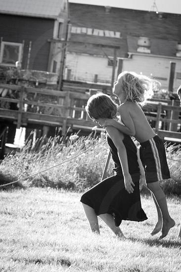 boy wearing black shorts riding girl's back photo