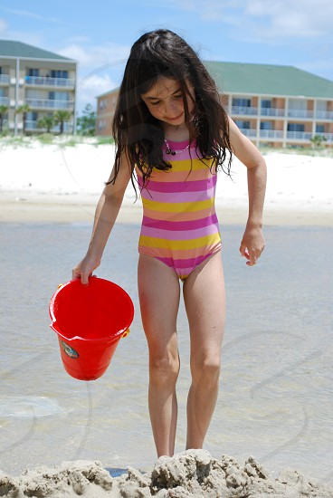 girl in swim suit carrying a red bucket photo