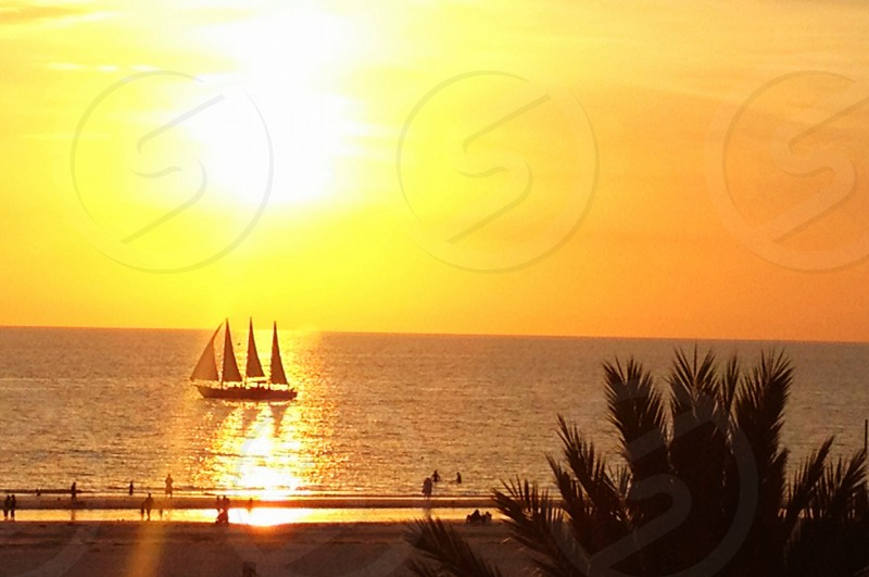 white sailboat on top of body of water during sunset photo