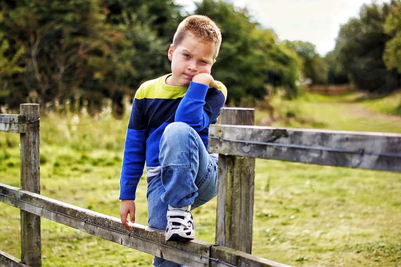 boy wearing yellow black and blue long sleeved crewneck shirt photo