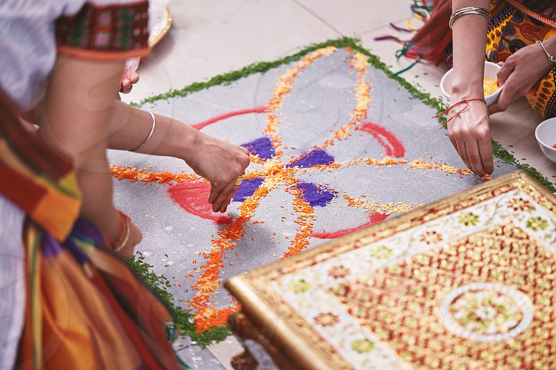 Women helps coloring tradition colorful rice art or sand art (Rangoli) on the floor with paper pattern using dry rice and dry flour with colored from natural pigments like sindoor haldi (turmeric) photo