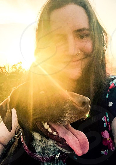 woman in black and multicolored shirt with medium short-coated black and white dog photo