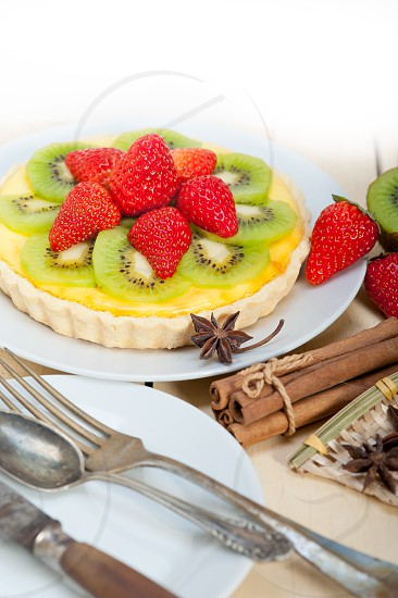 kiwi and strawberry pie tart with lemon custard cream and spices photo