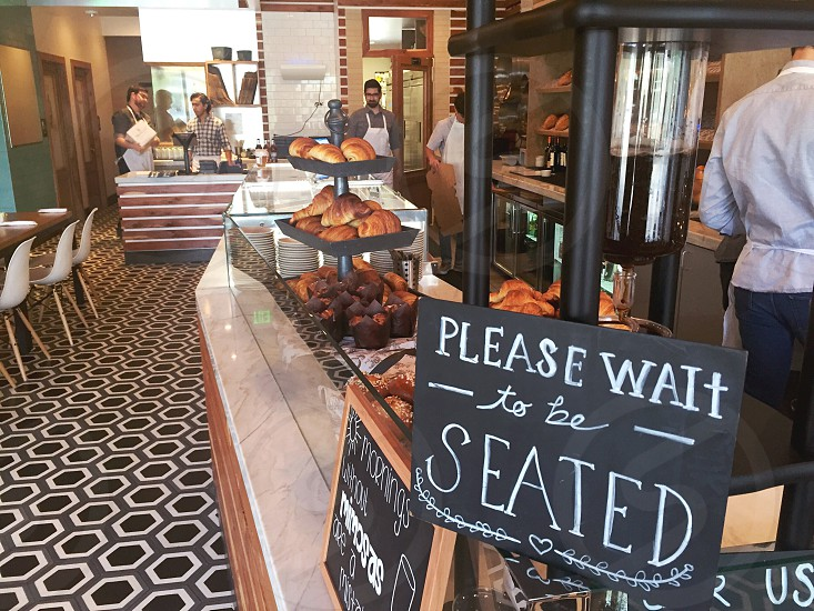 please wait to be seated signage top on glass display counter with different type of breads and 5 people in a counter photo