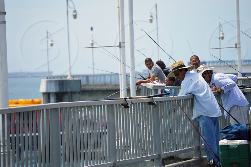 group of men fishing on port with rails during daytime photo