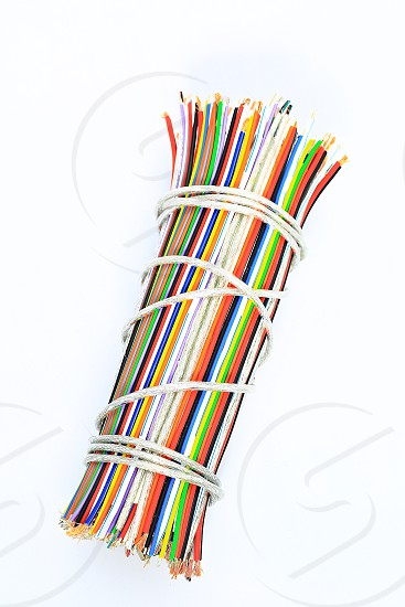 """Topic:""""Bundle of Wires"""" 11  This is an image of a bundle of electronic wires in multiple colors tied up with string with copy space and a clean white background. photo"""