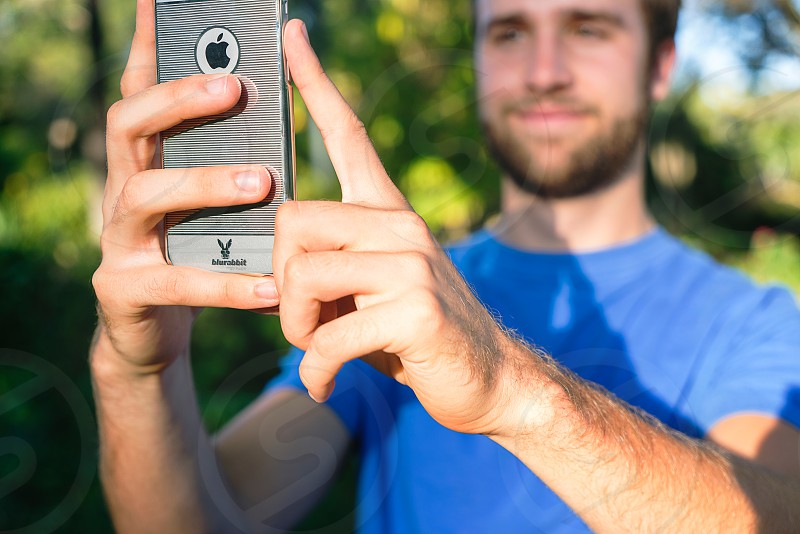 man using space grey iphone 6 during daytime photo