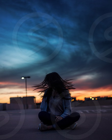 woman whipping her hair sitting on ground under black cloudy sky photo