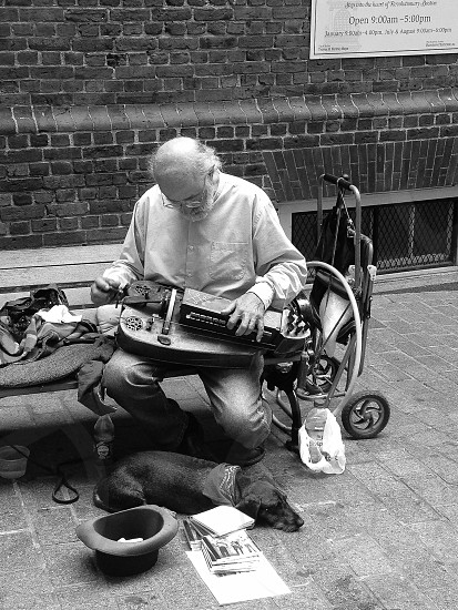 """On the way home I was sad to be leaving my friend and then I saw this man and his dog. I wanted to say to him """"you have just made me smile from the inside. Watching you simply play makes me realize that life really is wonderful and people are by nature good. The sun still shines on a cloudy day."""" What I did was say """"thank you"""" and throw him five bucks. And snap a picture.  photo"""