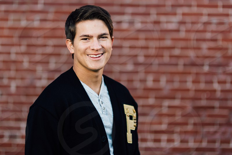 man in black p jacket smiling taking photo near brown wall bricks during daytime photo