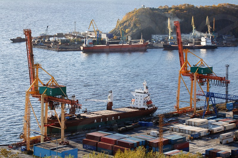 PETROPAVLOVSK-KAMCHATSKY CITY KAMCHATKA PENINSULA RUSSIAN FAR EAST - OCTOBER 3 2017: View on ships at pier and port cranes on commercial seaport Petropavlovsk-Kamchatsky on shore of Avacha Bay. photo