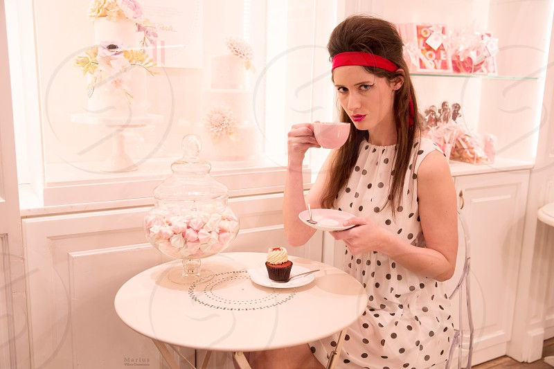 Sixties! Young woman enjoys coffee and cupcake in a nostalgic cupcake store! photo