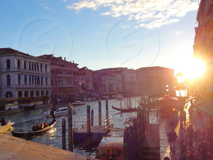 A life still on the canals of Venice during sunset featuring several gondolas. photo