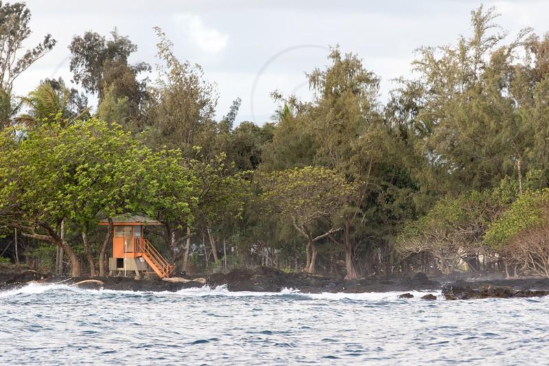 The orange lifeguard stand on Richardson Beach.  Hilo Big Island Hawaii. photo