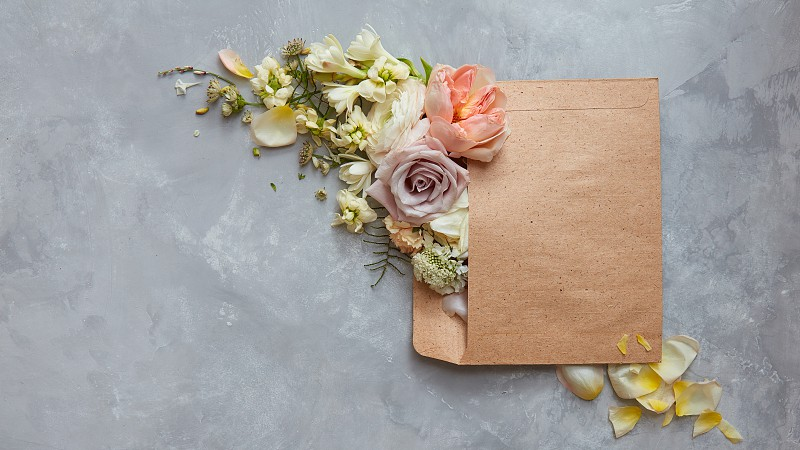 beautiful flowers in envelope on a stone gray background. Top view photo