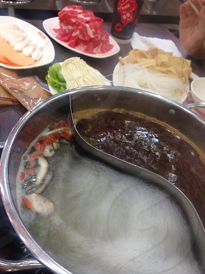 boiling water in a stainless steel round container beside raw meat and vegetable ingredients photo