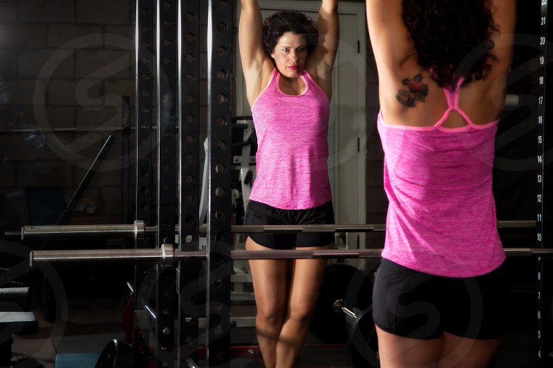 A fitness trainer looks at herself confidently in the mirror as she prepares to do chin-ups. photo