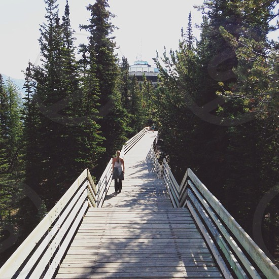 Woman walking down a wood bridge to a building in the trees photo