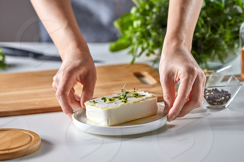 The girl's hands are holding organic cheese with healthy green sprouts in a plate on the kitchen table with fresh greens and copy space. photo