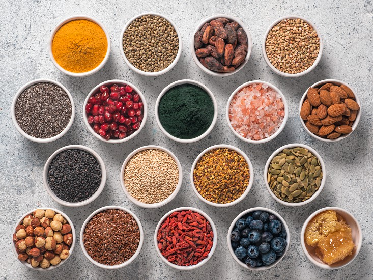 Various superfoods in smal bowl gray concrete background. Superfood as chia spirulina raw cocoa bean goji hemp quinoa bee pollen black sesame turmeric. Top view or flat-lay. photo