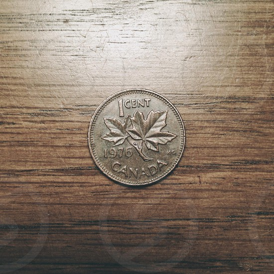 silver 1 cent 1976 canada round coin on brown wooden surface photo