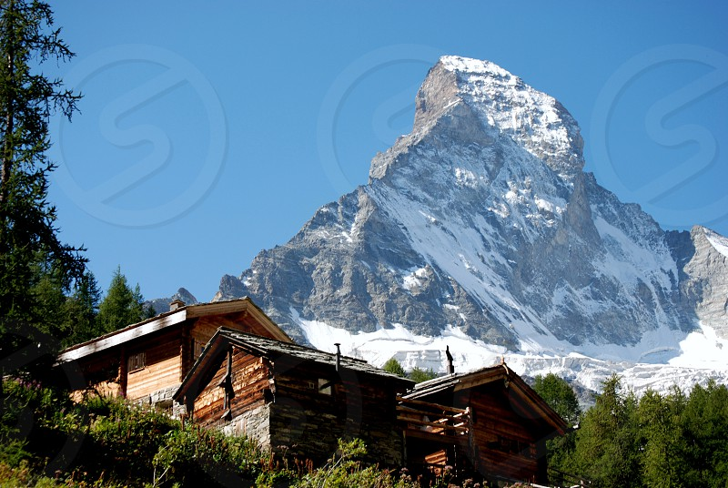 brown and black wooden house in distance glacier mountain under blue sky at daytime photo