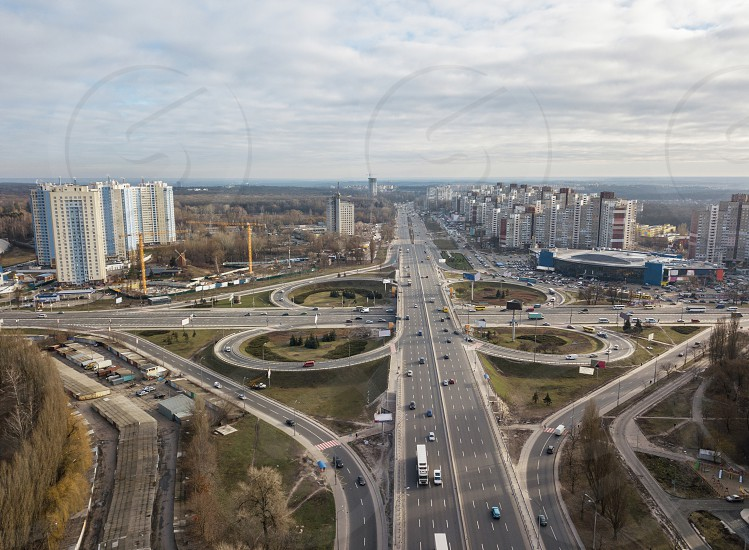 Aerial view of the drone on the Odessa square with highway in the form of a quatrefoil with passing cars and a modern city against a cloudy sky autumn day. Kiev Ukraine photo
