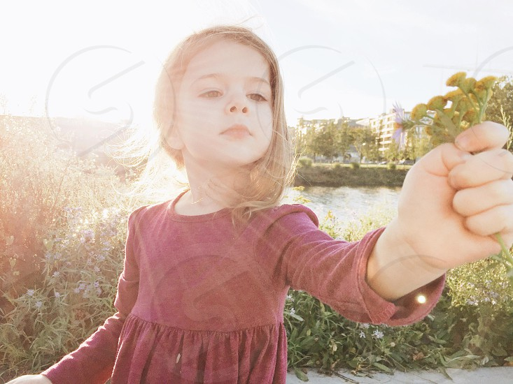 girl reaching out holding small green flowers photo