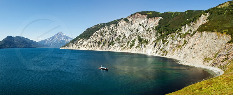 Stunning scenery autumn panorama landscape top view of steep mountainous coast of Pacific Ocean on unique nature of Kamchatka Peninsula on sunny day with clear blue sky. Eurasia Russian Far East photo