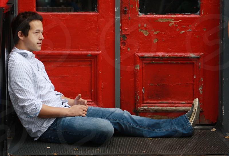Man Sitting in Front of Red Door photo