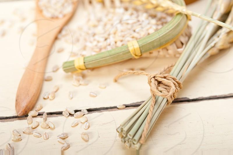 organic barley grains over rustic wood table macro closeup photo