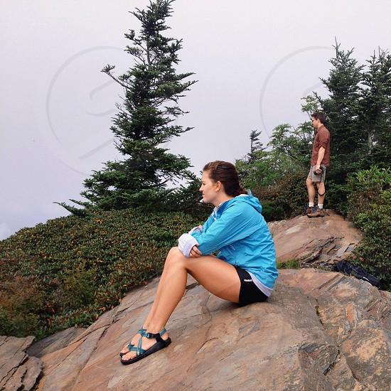 woman in blue jacket sitting on rock photo