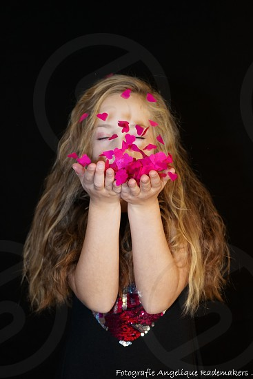 a young girl blowing confetti photo