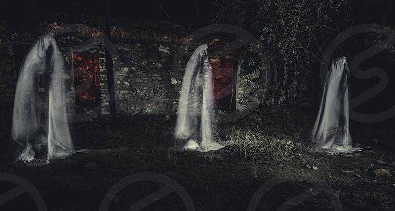 Three ghosts in front of old house with red lights in the forest photo