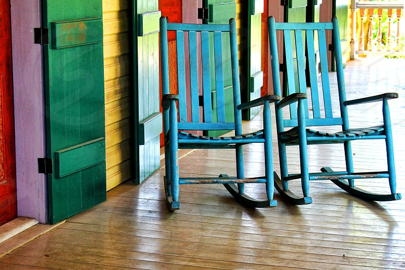 A pair of blue rocking chairs are on the colorful porch of a southern plantation. photo