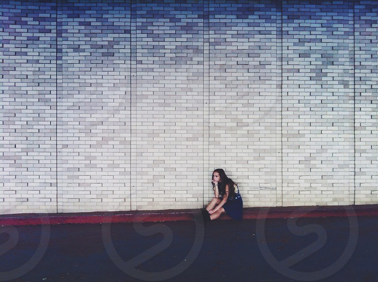 woman in white and black dress sitting in front of white brick wall photo