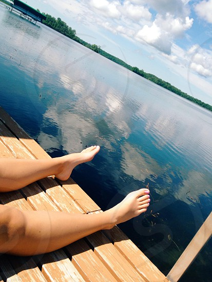 person laying on brown paneled surface beside body of water photo