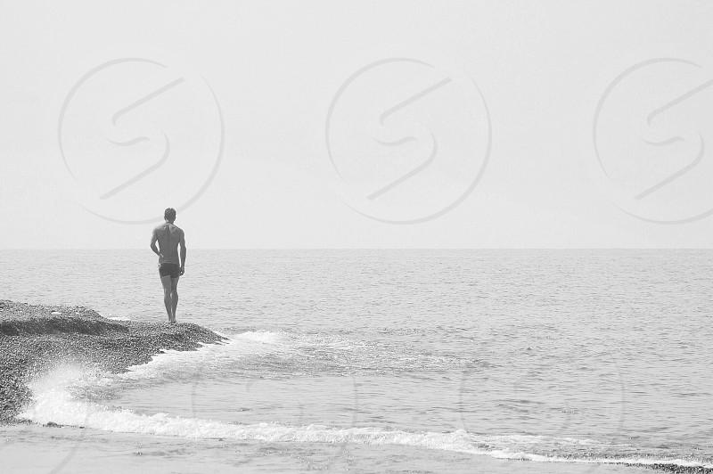man walking along beach shore photo
