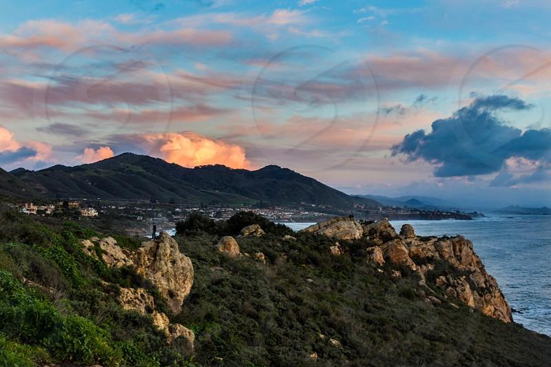 Sunset pink rocks green cliff mountain clouds cloud pink clouds ocean sea waves salt  photo