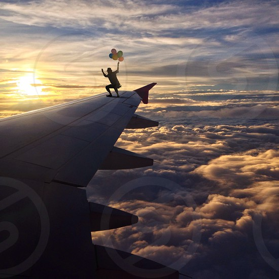 person holding balloons standing on airplane wing in sky photo