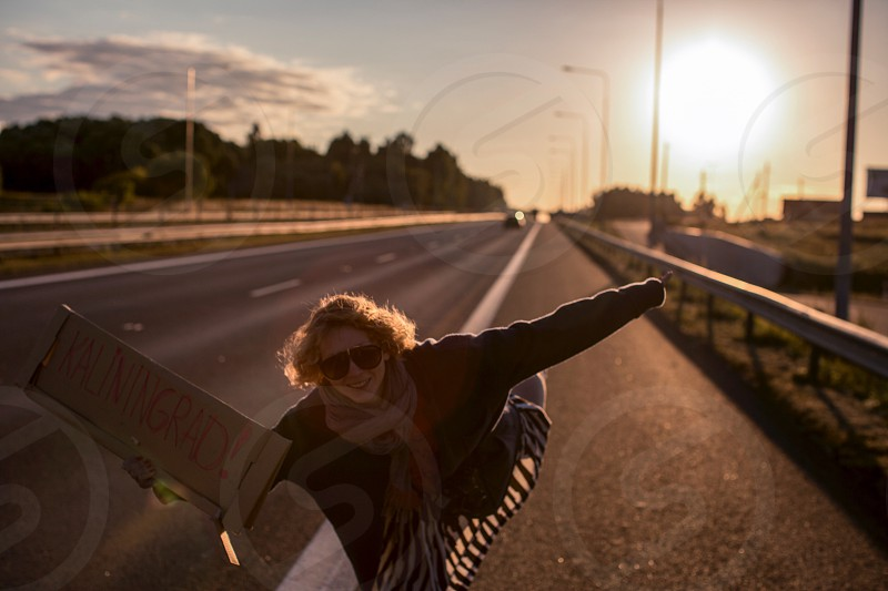 On the road road trip travel hitchhiking hitchhiker people person girl woman sunglasse sun sunshine sunset smile nice blonde blond hair young youth outdoor out air landscape traffic transportation cars photo