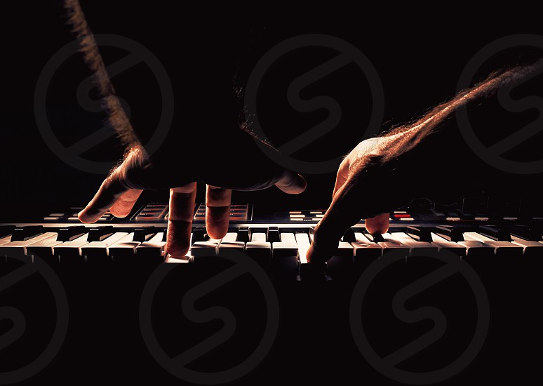 Playing a keyboard two male hands playing accentuated contrasts.   photo