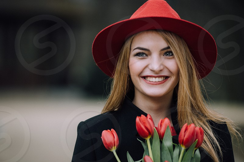 smiling red hair woman wearing a red hat and black jacket holding red tulips photo