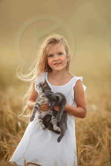 Little girl with two kittens on yellow field  photo