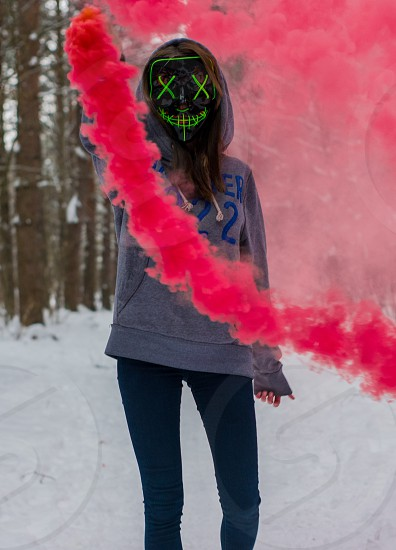 Female model with colorful smoke posing in the outdoors photo