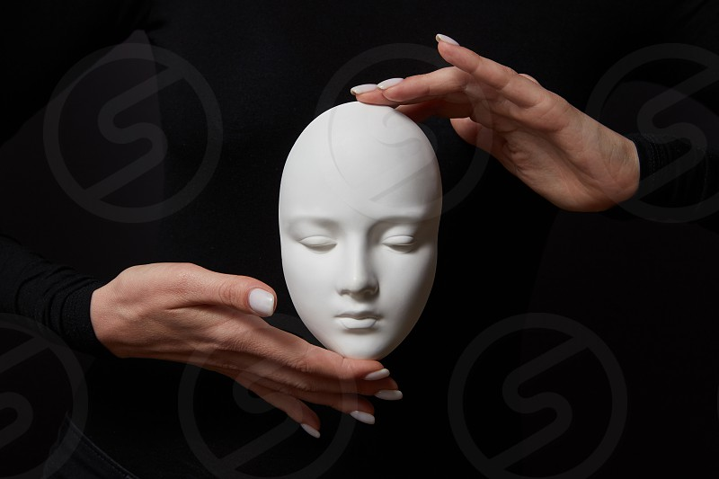 White plaster mask face is holding woman's fingers on a black background copy space. Concept social psychological masks photo